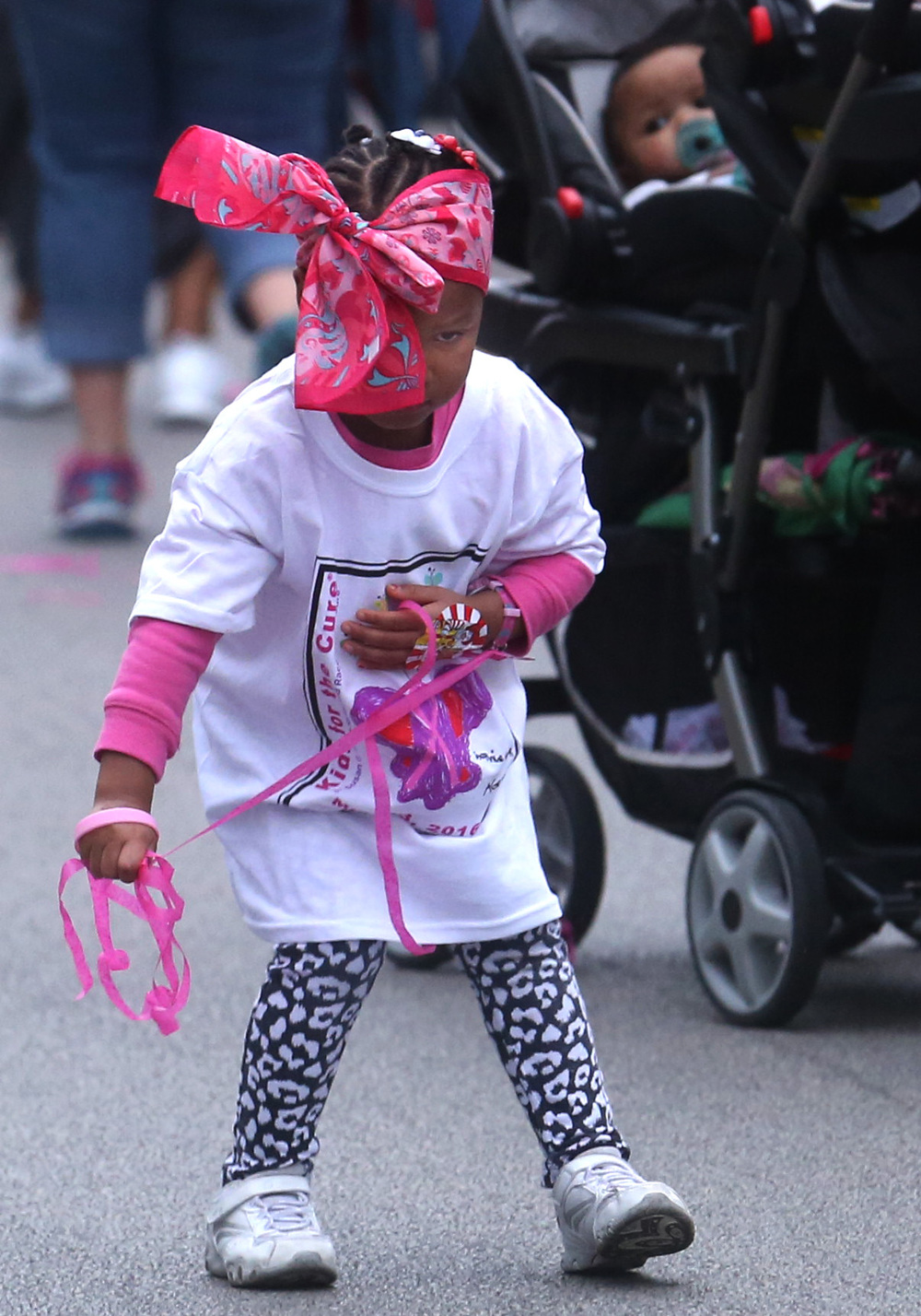 One young race participant coulden't resist collecting some of the pink streamers that ended up on the race course Friday night. David Spencer/The State Journal-Register