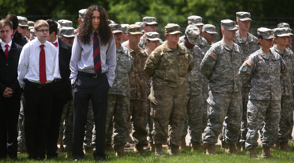 Some of the members of the Mt. Zion High School chorus at left, who later sang during the ceremony, stood along with some of the more than 100 Illinois National Guard soldiers from around the state. David Spencer/The State Journal-Register