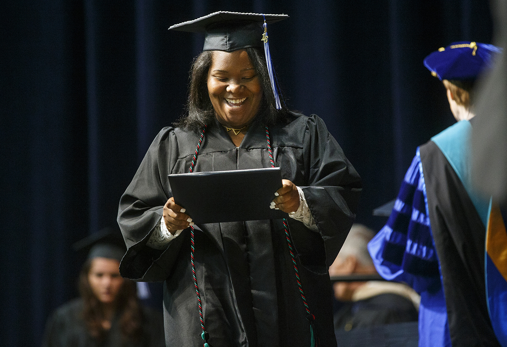 Chantrell Collier smiles as she looks down at her ceremonial diploma during the University of Illinois Springfield's 45th annual Commencement Ceremony at the Prairie Capital Convention Center Saturday, May 14, 2016. Ted Schurter/The State Journal-Register