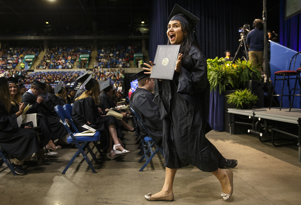 Aishwarya Thulasi Srinivasa celebrates as she walks back to her chair with her ceremonial diploma for her Masters in Management Information Systems during the University of Illinois Springfield's 45th annual Commencement Ceremony at the Prairie Capital Convention Center Saturday, May 14, 2016. Ted Schurter/The State Journal-Register