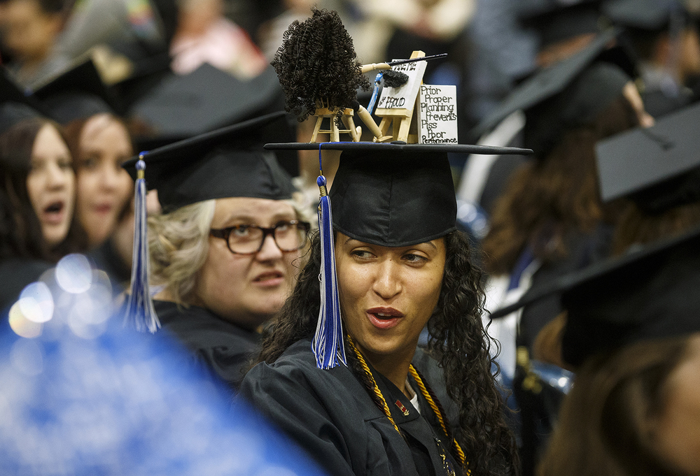 "Jessica Jones spent about an hour and a half and ""got a lot of glue on my fingers,"" while creating her graduation cap for the University of Illinois Springfield's 45th annual Commencement Ceremony at the Prairie Capital Convention Center Saturday, May 14, 2016. The hat featured an artist at an easel creating a work that said, ""Make me proud,"" and a few other phrases, including one from her dad about proper planning. Ted Schurter/The State Journal-Register"