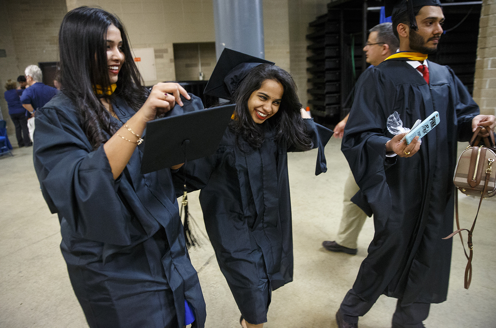 A trio of graduates hustles toward their seats as they try to get their caps on shortly before the University of Illinois Springfield's 45th annual Commencement Ceremony at the Prairie Capital Convention Center Saturday, May 14, 2016. Ted Schurter/The State Journal-Register