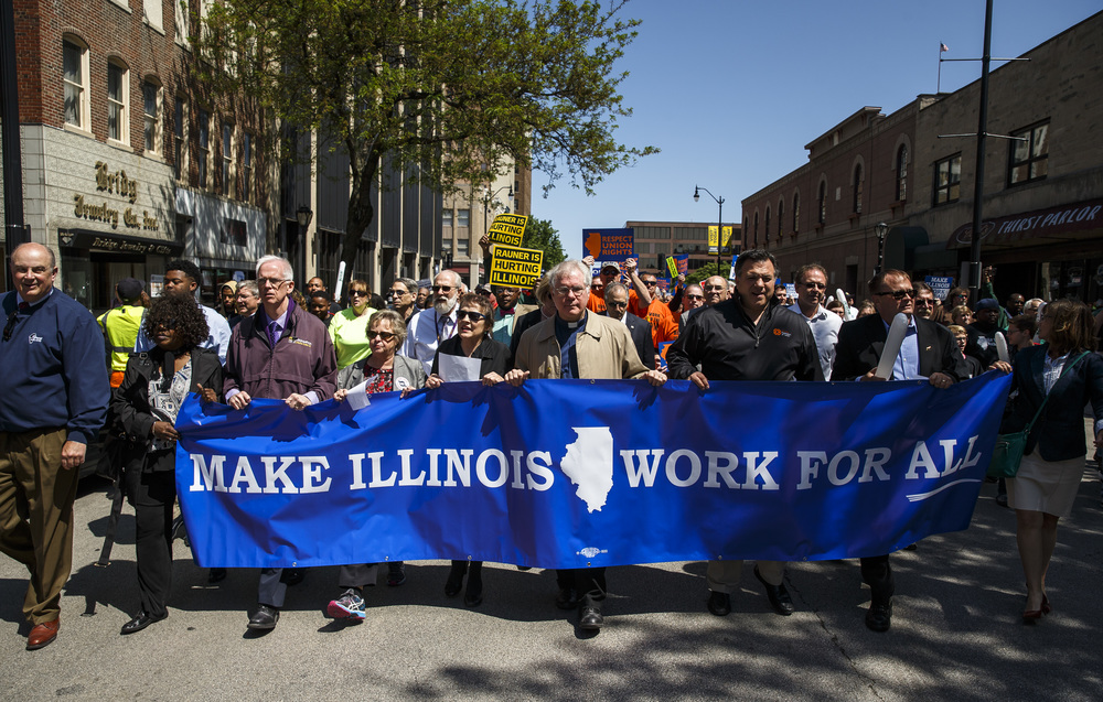 "Union organization leaders and community leaders march down Fifth Street with a crowd estimated at 8,000 as they make their way to the Illinois State Capitol for the ""Rauner is Hurting Illinois"" rally, Wednesday, May 18, 2016, in Springfield, Ill. Justin L. Fowler/The State Journal-Register"