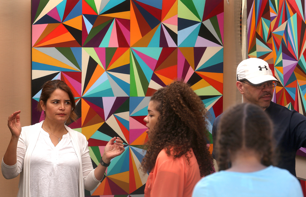 Chicago artist Carla Bank at left explains some of her geometric acyrlic paintings to a visitor to her booth at the fair on Saturday. David Spencer/The State Journal-Register
