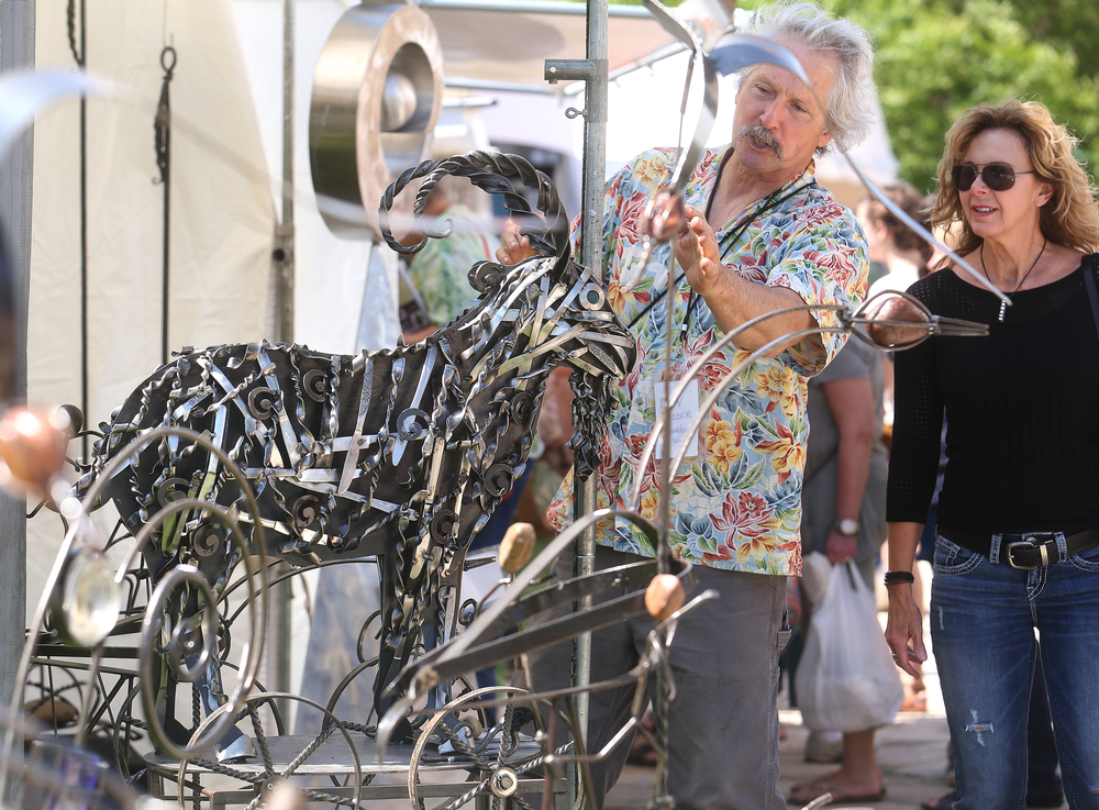 Fashioned from recycled steel and twisted stainless steel knives, this sculpture of a goat imagined as a large pull-toy on wheels is by Wisconsin artist Don Esser, seen here behind it showing off some features to a visitor. The asking price for the artwork is $1600.00. David Spencer/The State Journal-Register