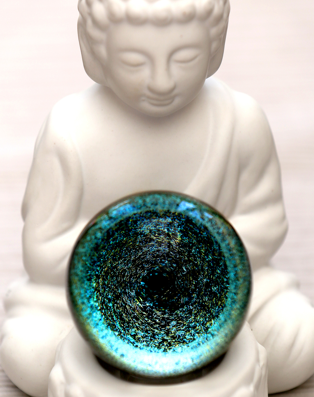 "Instead of a tealight, a miniature Buddha holds an oversized hand-blown glass marble known as a ""Vortex"" fashioned by Indiana glass artist Shane Caswell. David Spencer/The State Journal-Register"