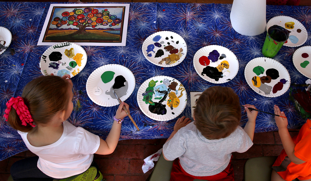 A childrens art tent sponsored by the Illinois State Musuem had budding artists each working on a miniature masterpiece to be collectively combined into a large mural-a mockup seen at upper left. David Spencer/The State Journal-Register
