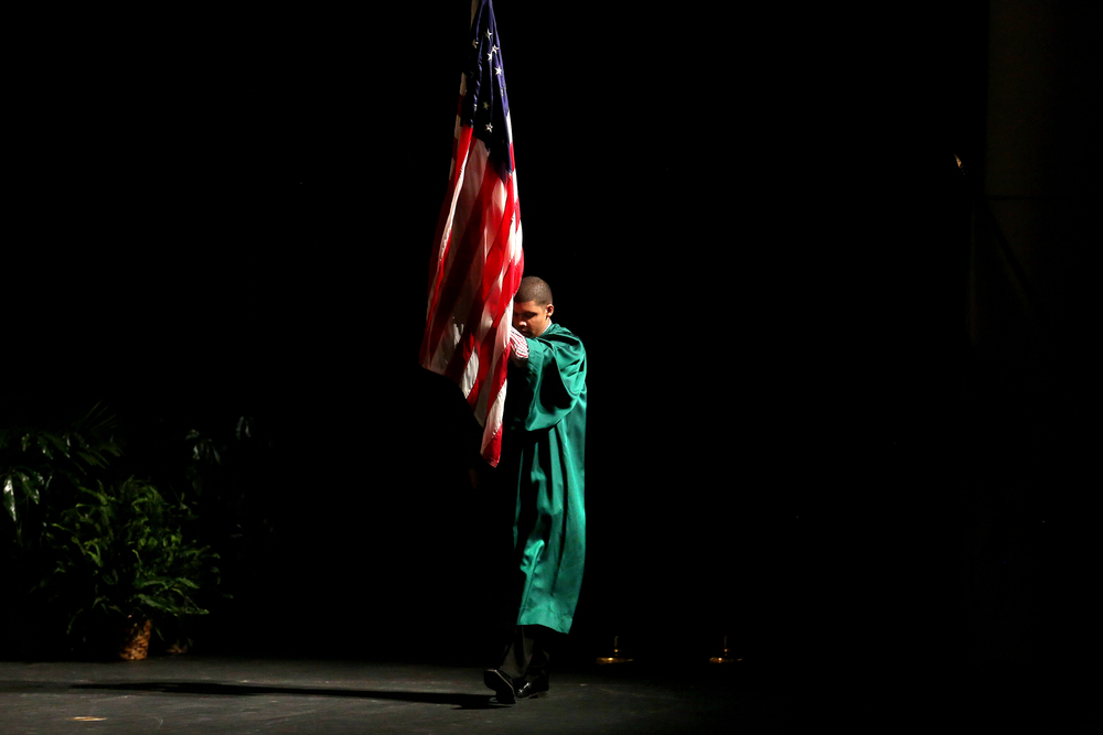A student from the class of 2017 leads the procession Saturday afternoon carrying the American flag across the stage inside Sangamon Auditorium. David Spencer/The State Journal-Register