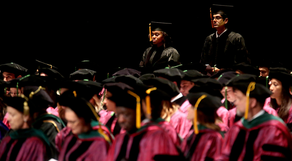 Two of the three candidates for the degree of Doctor of Philosophy in Molecular Biology, Microbiology and Biochemistry are seen here in back row: Cristal Hill at left and Vishnu Modur. Not seen is fellow candidate Ria Goswami. David Spencer/The State Journal-Register