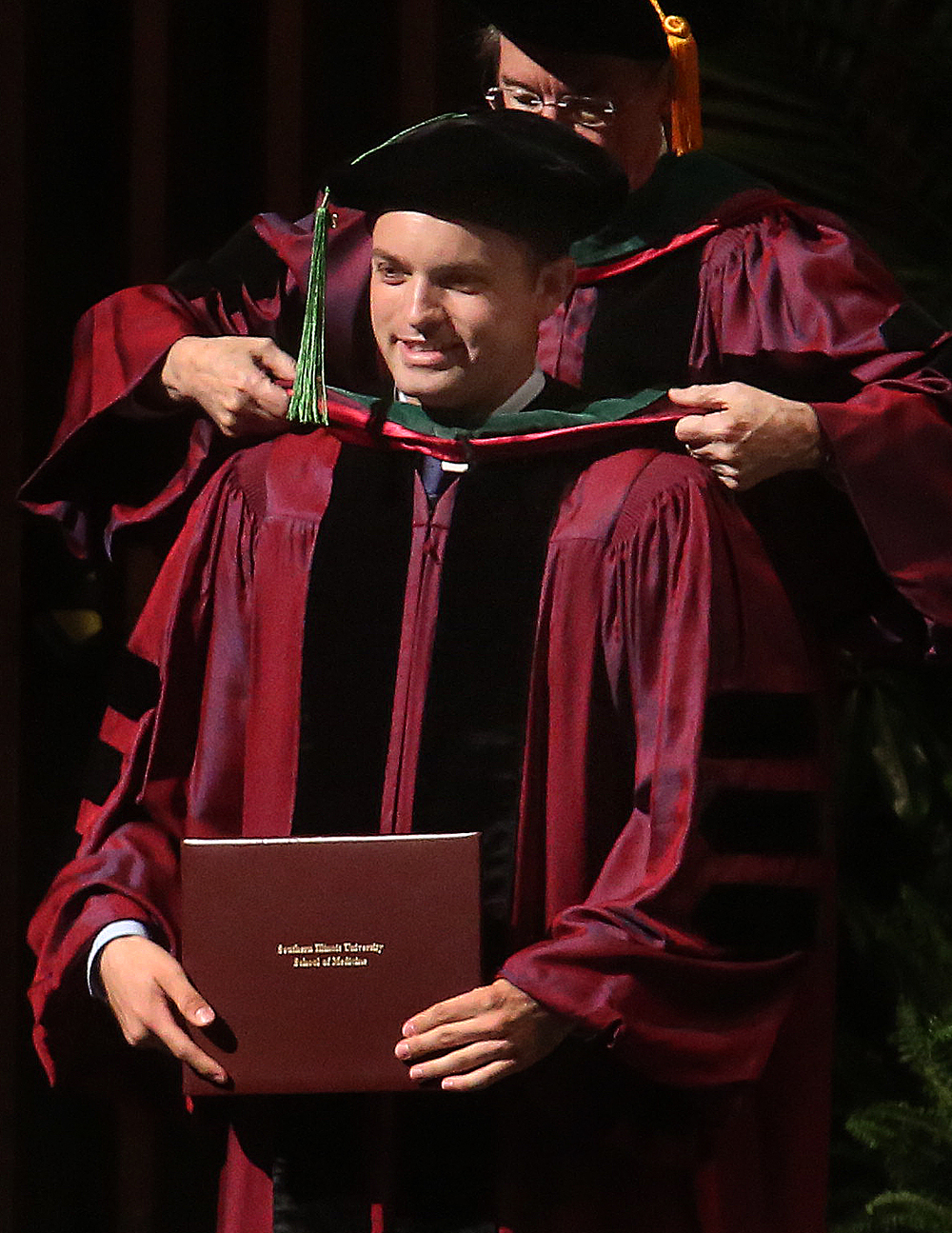 Chatham resident Tyler Fulks is hooded with his medical degree by former SIU Medical School dean and provost J. Kevin Dorsey. Fulks will be doing his residency in emergency medicine at the SIU School of Medicine affiliated hospitals in Springfield. David Spencer/The State Journal-Register
