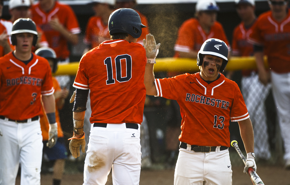Rochester's Tyler Fitzgerald (10) gets a high five from Rochester's Chase Kuntzman (13) after scoring a run on a balk to make it 3-2 Railsplitters in the 3rd inning during the Class 3A Springfield Regional Semifinals at Robin Roberts Stadium, Wednesday, May 25, 2016, in Springfield, Ill. Justin L. Fowler/The State Journal-Register