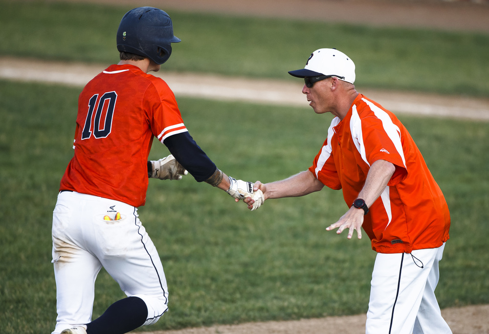 Rochester baseball head coach Matt Carlson gets a handshake from Rochester's Tyler Fitzgerald (10) as he heads to home plate after hitting a home run against Lincoln to tie the game in the 5th inning during the Class 3A Springfield Regional Semifinals at Robin Roberts Stadium, Wednesday, May 25, 2016, in Springfield, Ill. Justin L. Fowler/The State Journal-Register