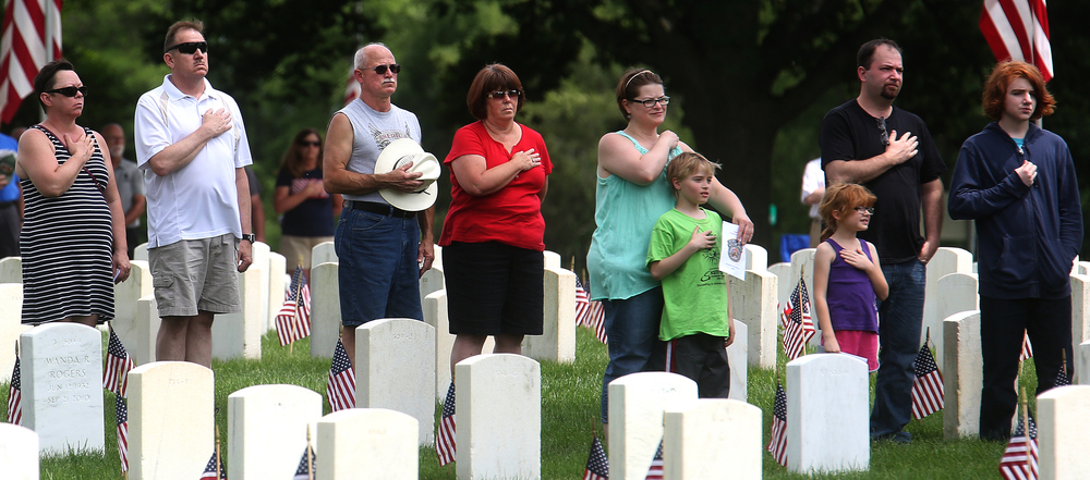 During the playing of the National Anthem, some of those attending the ceremony could be seen standing among headstones with hands across their hearts. David Spencer/The State Journal-Register