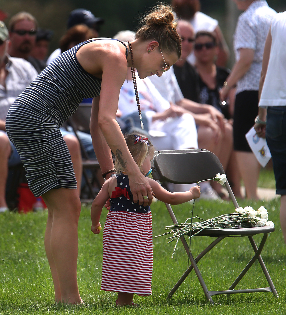 During the Vacant Chair ceremony, the littlest one taking part places a white carnation on the chair, symbolizing those veterans and servicemen who made the ultimate sacrifice and did not return home. David Spencer/The State Journal-Register