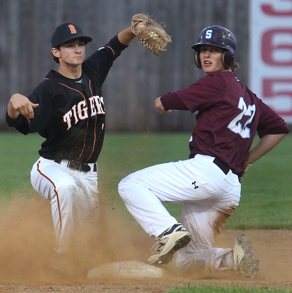 Tigers shortstop Rick Dour and Spartans baserunner Jake Pence look to the umpire for the call. Pence was called safe on the play. David Spencer/The State Journal-Register