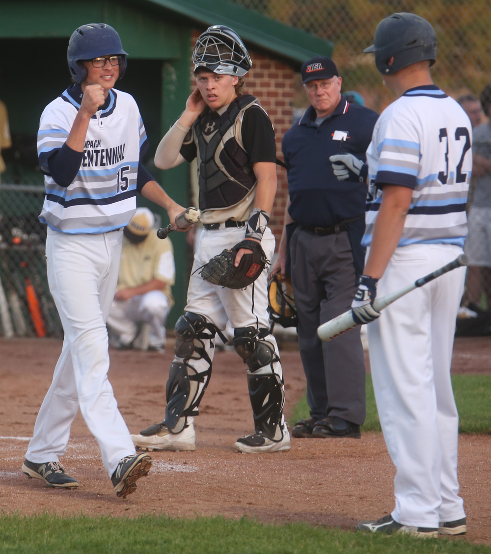 In second inning action, Champaign Centennial baserunner Luke Smith at left prepares to fist-bump teammate Chris Monroe after he scored the Chargers first run of the game. David Spencer/The State Journal-Register
