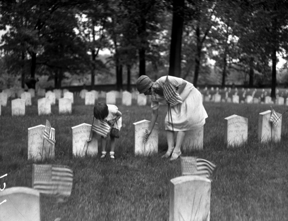 Woman and child placing flags at grave markers at Camp Butler National Cemetery, May 30, 1929. Illinois State Journal glass plate negative/Sangamon Valley Collection at Lincoln Library. All Rights Reserved, The State Journal-Register. C-98-086  neg# 157  