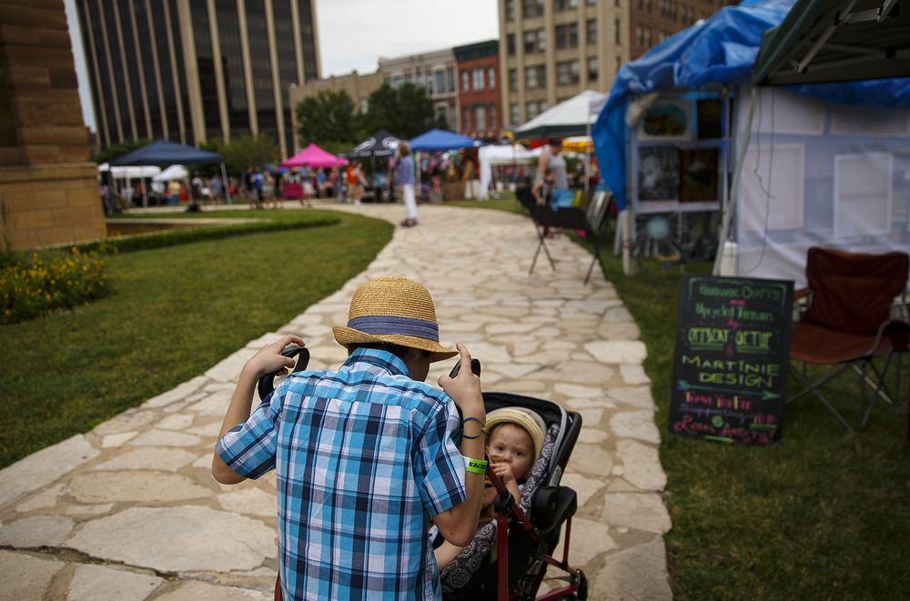 Arthur Wonneberger leans over and checks on his little sister Charlotte as they browse the art fair at the SoHo Music Festival in downtown Springfield Friday, June 3, 2016. Ted Schurter/The State Journal-Register