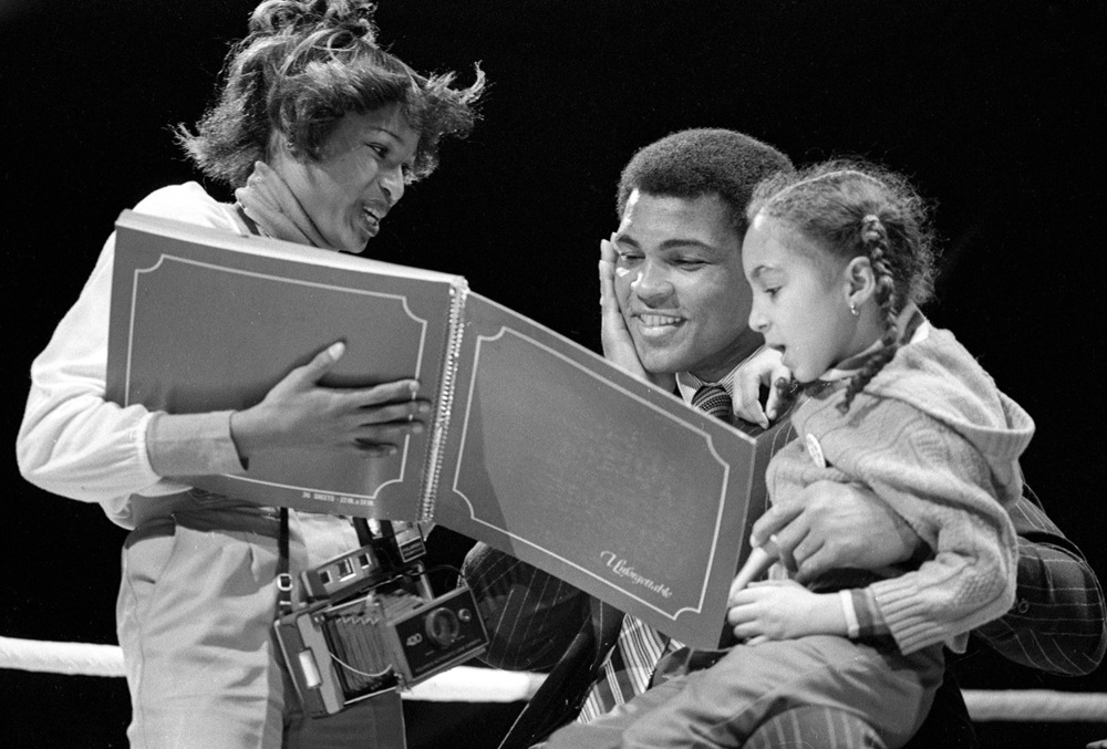 A guest shows Muhammad Ali a scrapbook during his a benefit for the Youth Service Bureau at the Illinois State Armory, Feb. 25, 1978. File/ The State Journal-Register