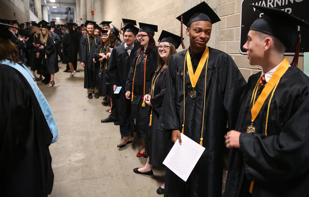 Class Salutatorian Eric Mason at center speaks with class Valedictorian Thomas Dane Jr. at right before they processed Saturday morning along with their fellow soon-to-be graduates lined up behind them. David Spencer/The State Journal- Register