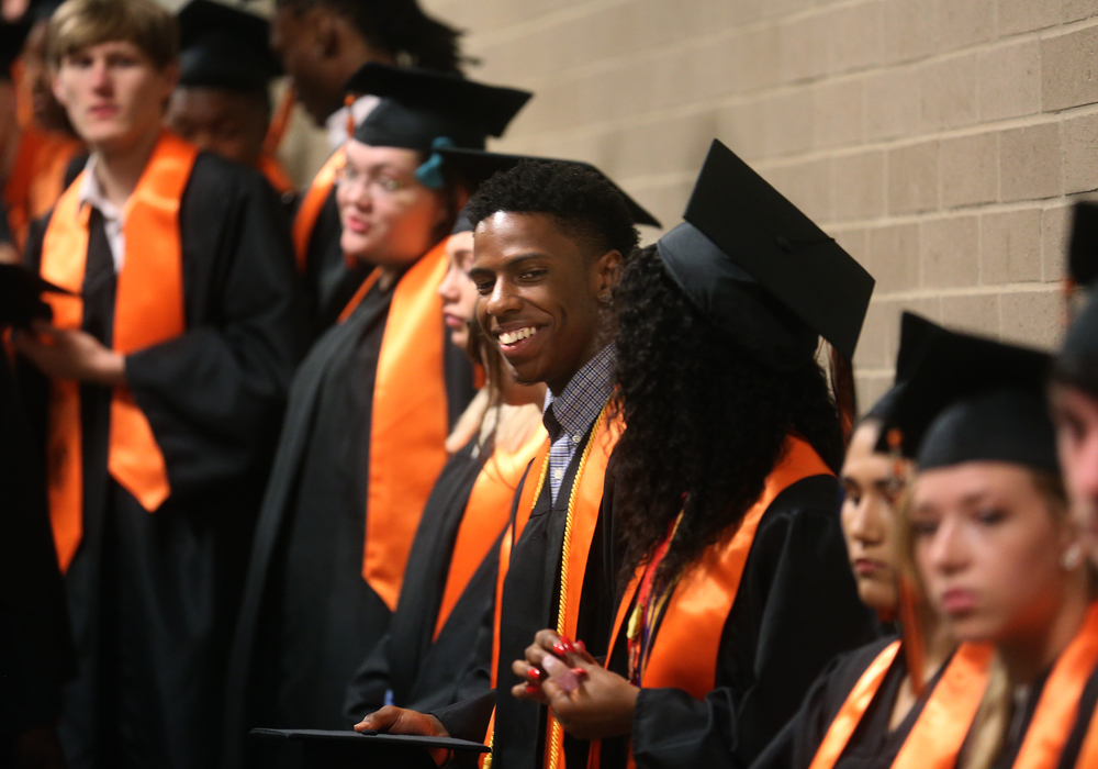 Soon-to-be Lanphier graduate Xavier Bishop laughs at center before processing with his fellow students Saturday morning. David Spencer/The State Journal- Register