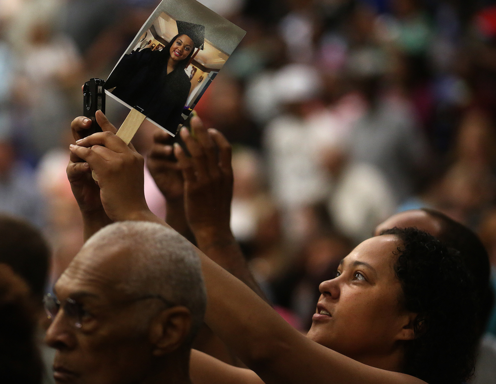 One family member took photos in the audience while holding aloft a photograph of a Lanphier graduate.David Spencer/The State Journal- Register