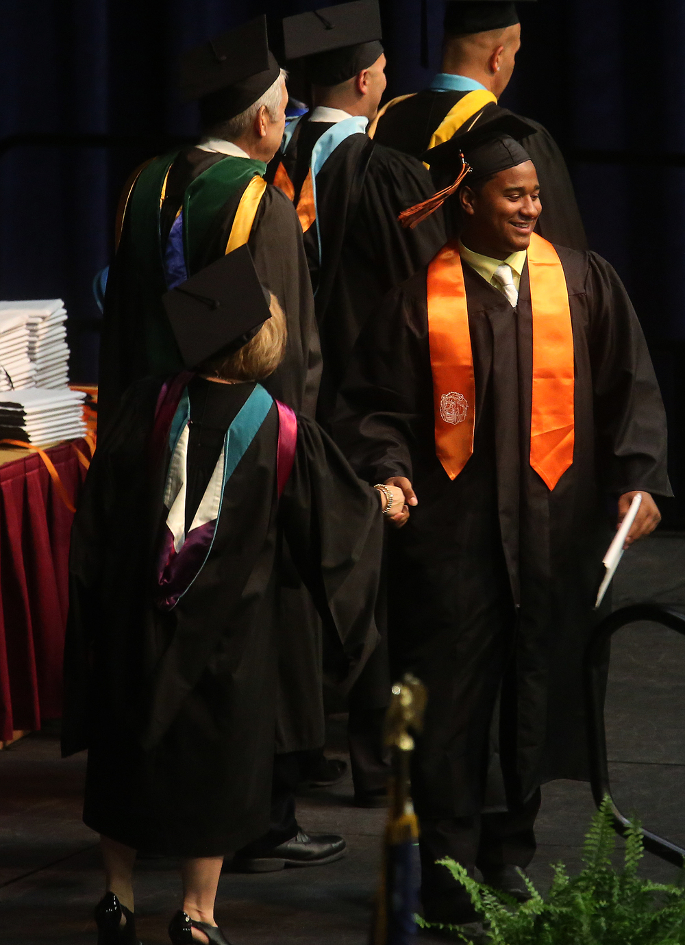 Springfield District 186 Superintendant Jennifer Gill at left shakes hands with a Lanphier graduate on stage Saturday. David Spencer/The State Journal- Register