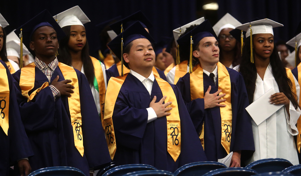 Some of the soon-to-be graduates stood and held hands to their hearts during the playing of the National Anthem. David Spencer/The State Journal- Register