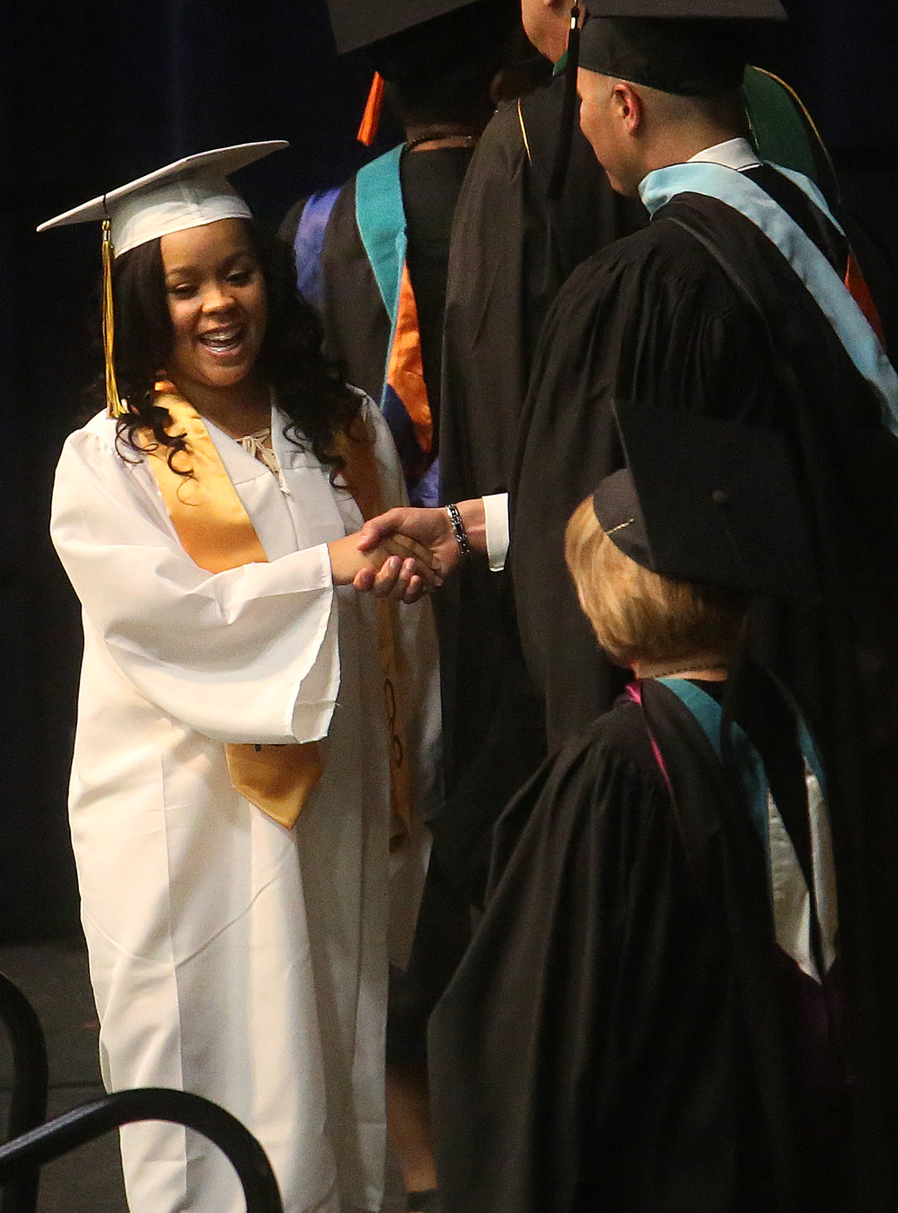 A student receiving her diploma shakes the hand of Springfield School Board President Adam Lopez Saturday. David Spencer/The State Journal- Register