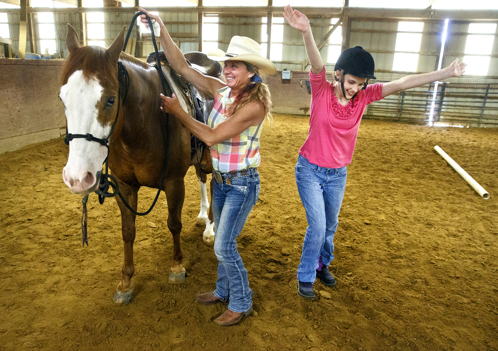 Jenna Allen is jubilant after a riding session with Vegas at Boyer Training Stables near Cantrall Friday, May 27, 2016. The bond between Allen, who has autism, and the former cattle horse is incredible, according to Becky Boyer, left, who assists Allen with the horse. Ted Schurter/The State Journal-Register