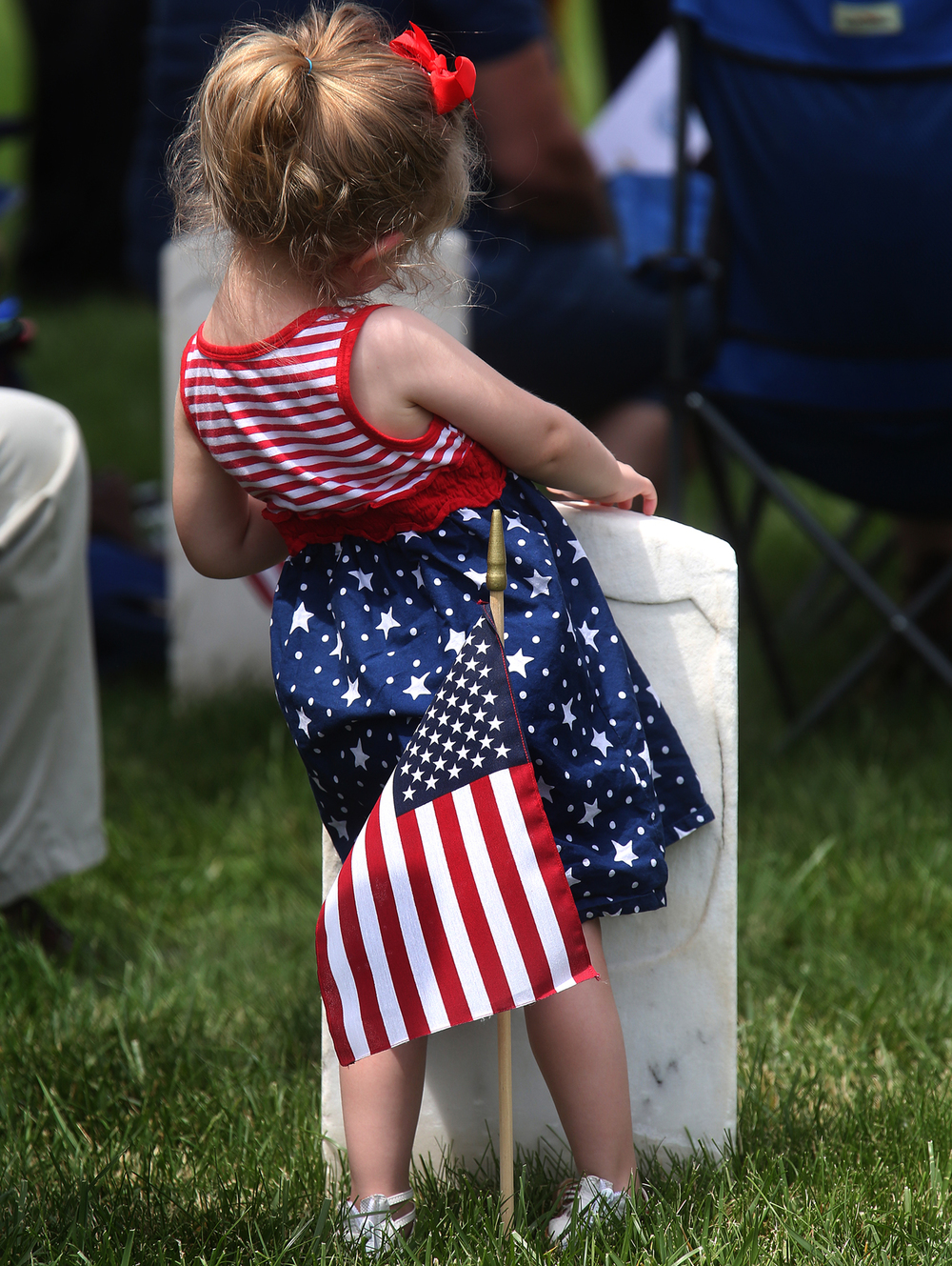 One youngster could be seen wearing a very patriotic dress fitting the occasion of Memorial Day as she balanced against a headstone during the ceremony. WWII veteran Vince Speranza of Auburn, who served in the 101st Airborne Division, was the keynote speaker at the annual Memorial Day Ceremony held at Camp Butler National Cemetery in Springfield on Monday afternoon, May 30, 2016. David Spencer/The State Journal-Register