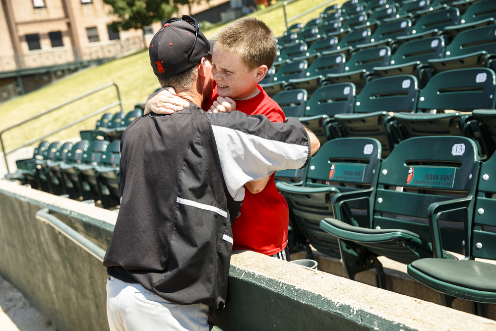 Assistant coach Tim Elliott hugs his son, Jacob, 11, after the Senators defeated Bartonville Limestone 13-0 in five innings in the IHSA Class 3A State Tournament semifinals at Silver Cross Field, Friday, June 10, 2016, in Joliet, Ill. Justin L. Fowler/The State Journal-Register
