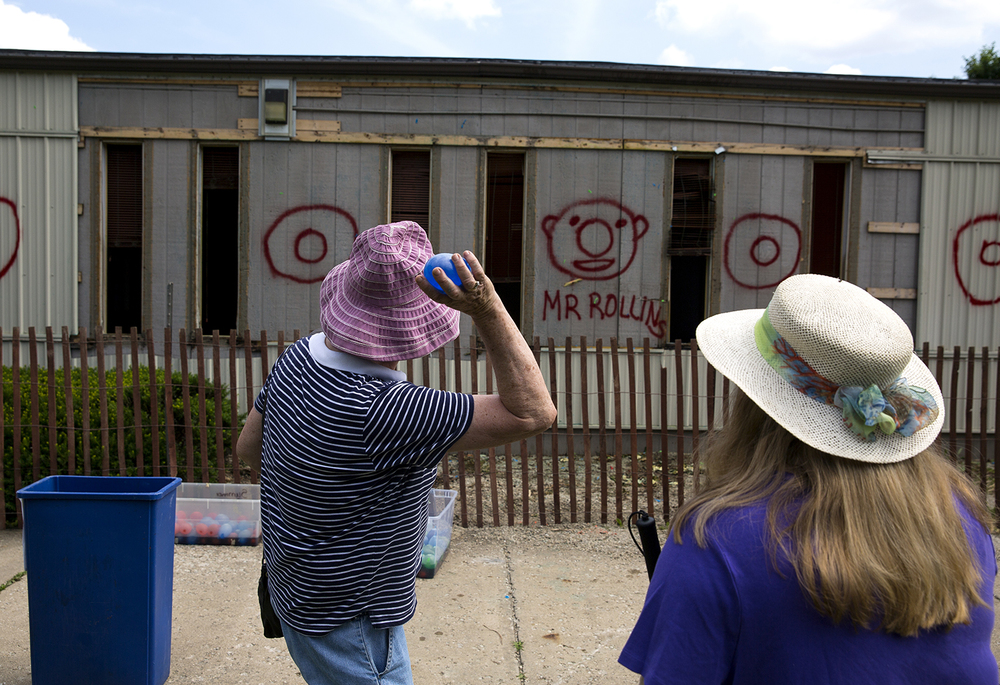 Shirley Springer winds up to throw a water balloon at one of the temporary classrooms on the Lutheran High School campus Saturday, June 11, 2016 before it was demolished during a party to celebrate the end of the well-used buildings. Construction of a new addition to the school will begin this fall. Springer's son, Michael, graduated from the school in 2004. Rich Saal/The State Journal-Register