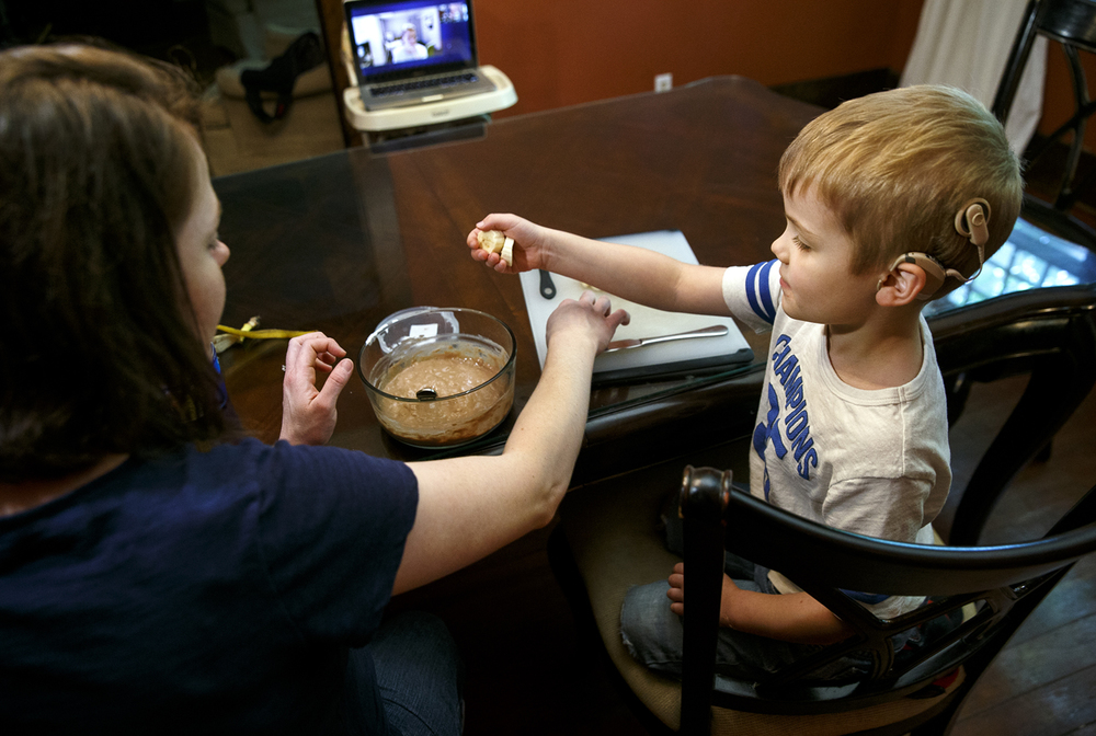 David Heady creates banana Nutella sandwiches with his mom Cheryl during a telemedicine call with Caroline Montgomery, a Cochlear Implant Education Coordinator at SIU School of Medicine, visible on the video call on the laptop in the background, Monday, June 6, 2016. The school is expanding the number of sites and patients reached by its telemedicine network in central and southern Illinois. Through special equipment that allows SIU doctors in Springfield to see, hear, interact with and conduct various types of examinations, SIU is treating more and more patients in rural areas. Ted Schurter/The State Journal-Register
