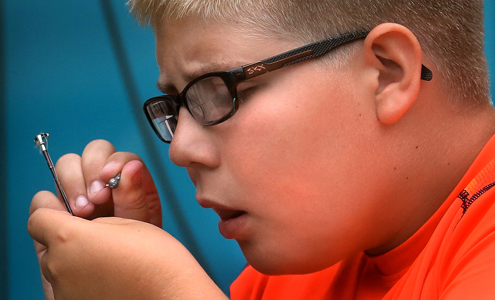 A fanatical fisherman, Carson Henley is patient while attaching a sinker to a fishing line but needs to be close while doing it as he is dependant on one eye when doing it in front of his Taylorville home on Friday, June 3, 2016. Henley was getting ready for a fishing derby for special needs children held this past Saturday at the Taylorville Marina. Carson Henley, 9, of Taylorville, has had severe eye disease after being born with congenital glaucoma. Now reliant on one eye after losing his other to surgery nearly three years ago, he hopes to do a few things as a sighted person before going blind. Among other things, Henley's family is hoping Carson can do things like take in a Cubs-Cardinals game at Wrigley Field, see Soldier Field, walk on an ocean beach and ride a trolley car in San Francisco. David Spencer/The State Journal-Register