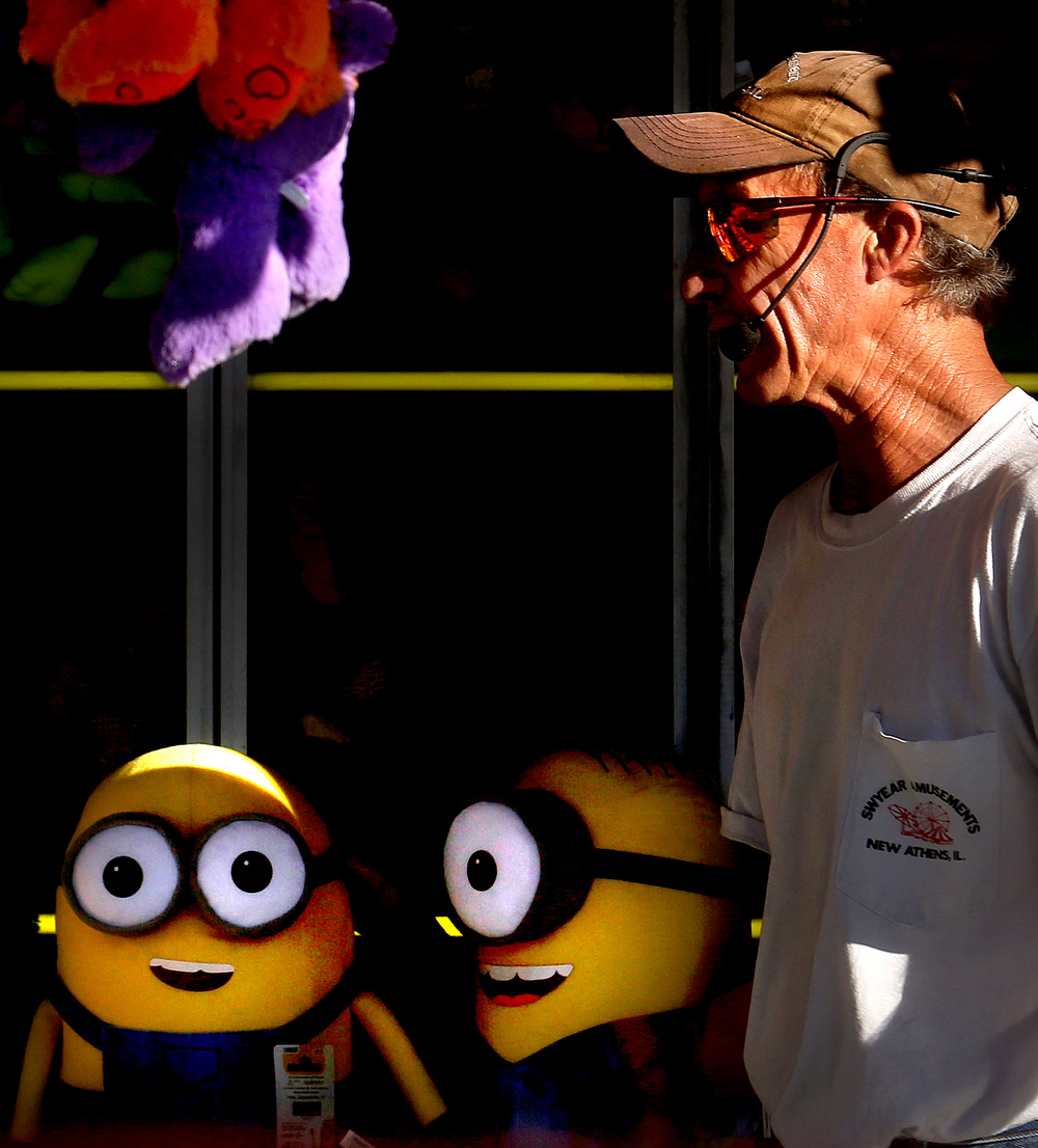 An employee of Swyear Amusements in the carnival games area ably directed his opinion to this photographer via  his trusty microphone headset during a free moment at the Sangamon County Fair in New Berlin, Ill on Thursday, June 16, 2016. David Spencer/The State Journal-Register