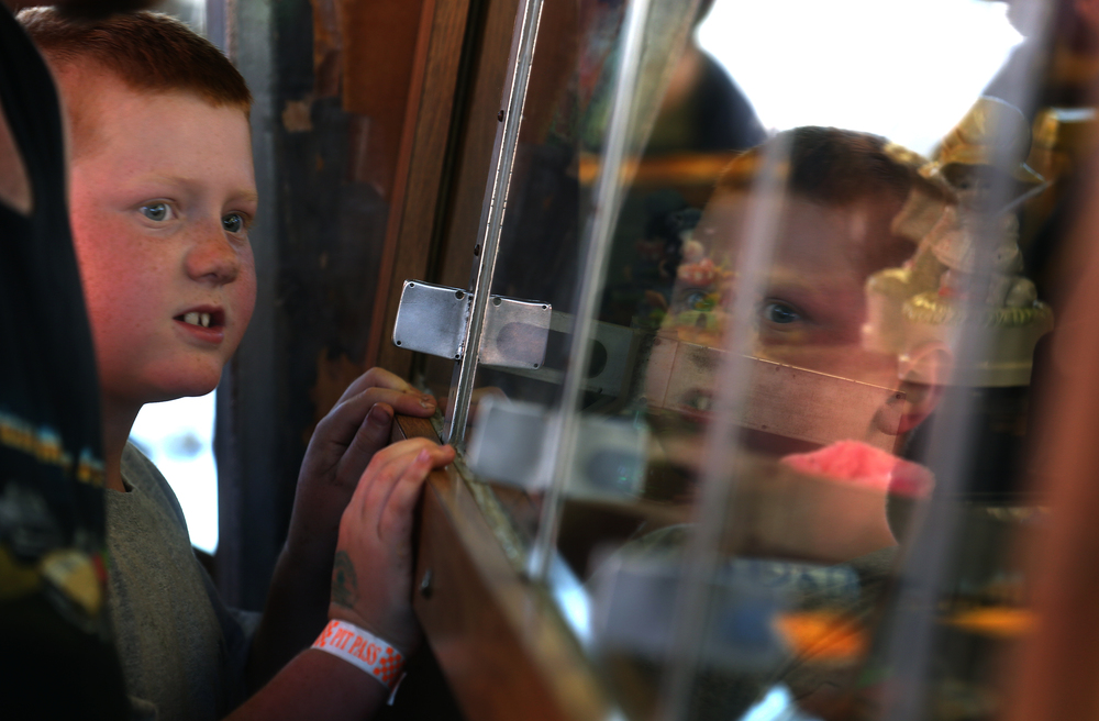 Prizes behind glass at one of the carnival games get the interest and reflection of one young fairgoer at the Sangamon County Fair in New Berlin, Ill on Thursday, June 16, 2016. David Spencer/The State Journal-Register