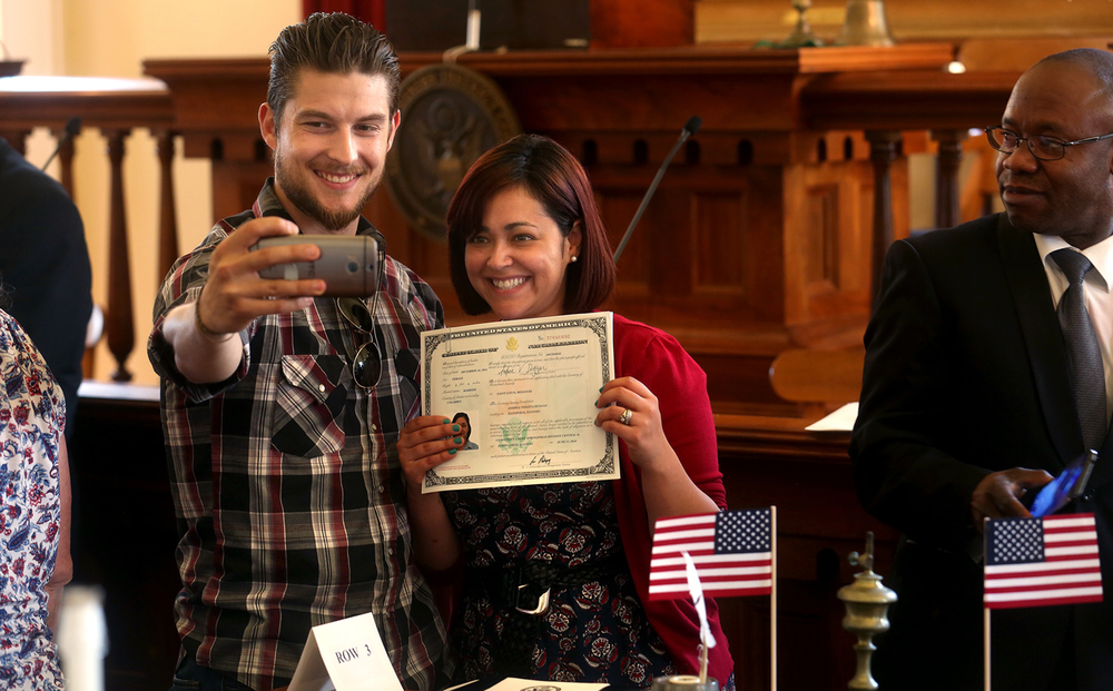 New American citizen Andrea Duggan of Illiopolis holds her Naturalization certificate as she gets her photo taken by husband Charlie Duggan at the conclusion of the ceremony. Andrea Duggan is originally from Columbia. A Naturalization ceremony was held for 27 new citizens from 16 different countries at the Old State Capitol in Springfield on Friday, June 17, 2016. David Spencer/The State Journal-Register