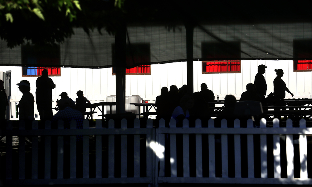 Fair goers are silhouetted under and beyond a performance pavilion at the Sangamon County Fair in New Berlin, Ill on Thursday, June 16, 2016. David Spencer/The State Journal-Register