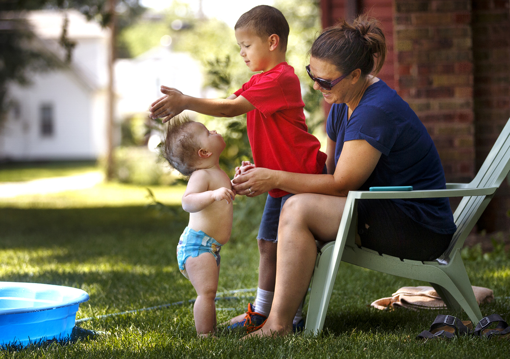 Joshua Phillips forms his brother Caleb's hair into an impromptu mohawk as they relax near a pool in the shade of their Enos Park yard with their mother Kellie on Monday, June 20, 2016. Ted Schurter/The State Journal-Register