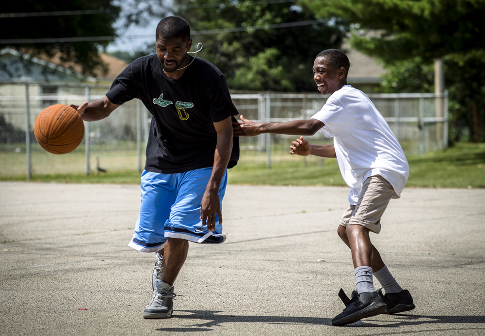 Timothy Price Jr. is all smiles as he tries to shut down his father, Timothy Price Sr., left, on defense during a game of 1-on-1 during the Juneteenth Celebration at Comer Cox Park, Sunday, June 19, 2016, in Springfield, Ill. Price Jr. defeated his father 7-5 by outshooting him from the perimeter. Justin L. Fowler/The State Journal-Register