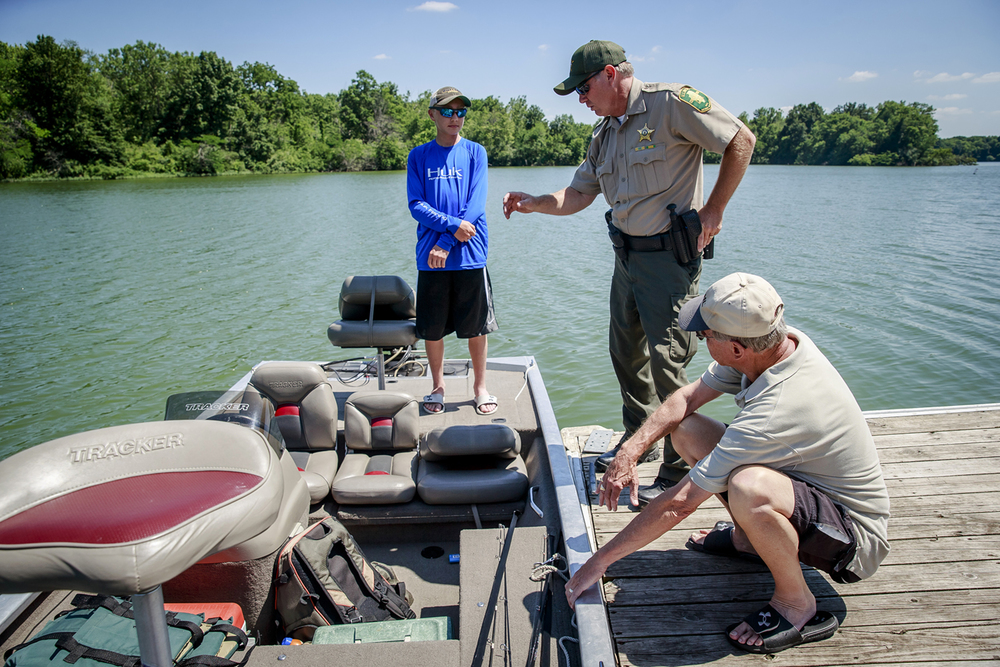 Illinois Conservation Police Officer Kevin Bettis, center, goes through a safety check with Dan Drewes, of Chatham, Ill., and his grandson, Griffin Harms, at boat launch on Sangchris Lake State Park, Friday, June 17, 2016, southeast of Rochester, Ill. Illinois boaters are required to have certain safety items on board at all times including flotation devices, a whistle and a fire extinguisher. Justin L. Fowler/The State Journal-Register