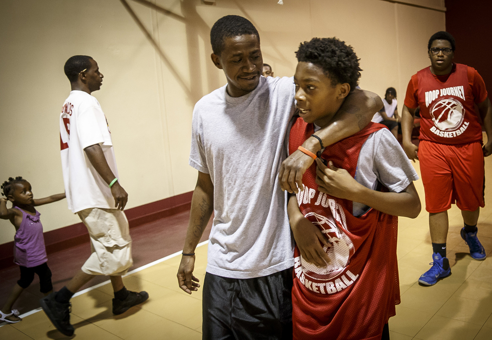 Terrion Murdix, 15, a point guard for Team Jordan, gets a hug from coach Phillip Jordan after the team won their game for the night during The Outlet's Hoop Journey summer basketball league at the Abundant Faith Christian Center, Monday, June 20, 2016, in Springfield, Ill. Justin L. Fowler/The State Journal-Register