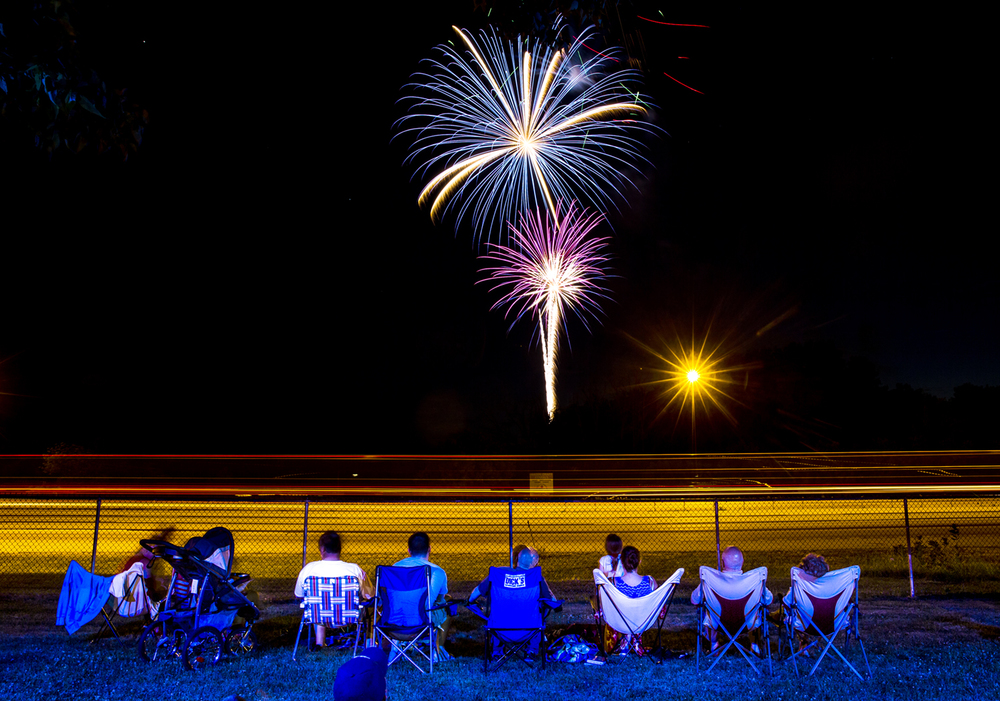 Fireworks explode over the sky as the blur of car lights along I-55 from a long exposure silhouette the spectators taking in the fireworks from the Illinois State Police Academy during Rock the Dock on Lake Springfield, Friday, June 24, 2016, in Springfield, Ill. Justin L. Fowler/The State Journal-Register