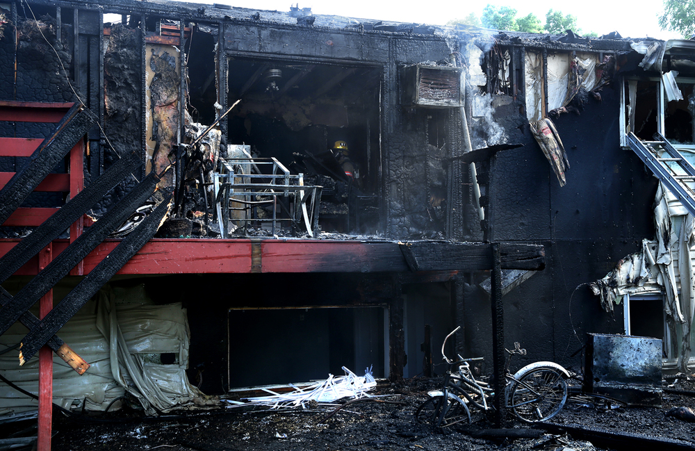 A rear view of the burned out apartments in unit D of the complex is seen here shortly after the fire was put out Tuesday afternoon. A fire of undetermined origin burned out apartments at the Village Park Apartments at 3241 South Douglas Ave. in Springfield on Tuesday, June 21, 2016.  David Spencer/The State Journal-Register