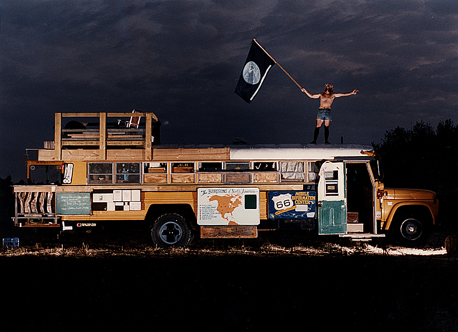"In 1991, I photographed Rochester area artist Robert ""Bob"" Waldmire (1945–2009) holding the Earth flag atop his home: a converted 1966 Chevrolet school bus while he points to the west-the direction of his travels on America's fabled Mother Road: Route 66. Included as a portrait I did on prairie artists for Heartland Magazine, Bob was the ultimate free spirit, a self-sufficient vegan and unconventional soul who struck me as completely satisfied with what I would describe as a spartan existence. With an oil lamp and healthy supply of rapidograph-style calligraphy pens at his side, Bob worked into the night inside the bus creating artwork of his beloved Route 66 and his many travels on it. Along with his 1972 VW van, the bus, significantly added to since this photo was taken, is now permanently parked for all to visit outside the Route 66 Museum and Hall of Fame in Pontiac, Ill. The museum describes these two vehicles as ""the physical manifestations of Bob's dedication to Route 66 and his art which celebrated it."" David Spencer/The State Journal-Register"