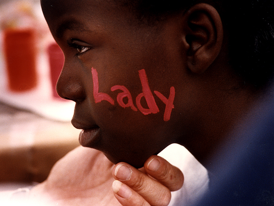 "As part of the second annual Harmony in the Neighborhood festival held at Springfield's John Hay Homes in August, 1992, 12-year-old Quavetta Tanner has the name ""Lady T"" painted on the side of her face in neon pink by District 186 teacher Patti Owens. David Spencer/The State Journal-Register"