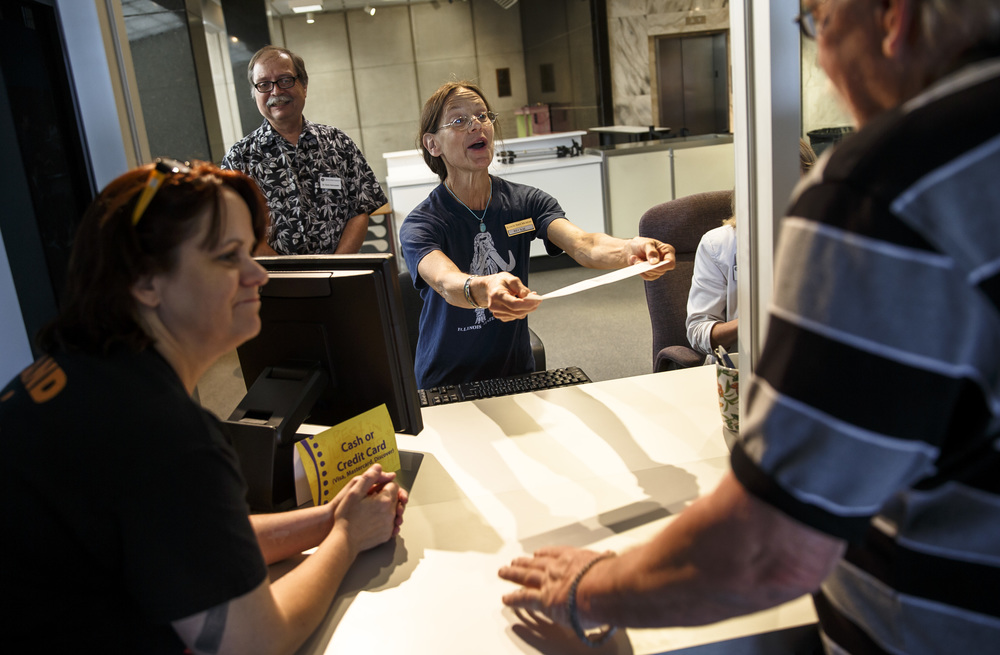 Staff member Beckie Dyer hands a ticket for entry over to Mike Parkhill for the new admission process at the Illinois State Museum, Saturday, July 2, 2016, in Springfield, Ill. The museum established a $5.00 admission fee for adults, but allows children age 18 and under, seniors and veterans free admission. Justin L. Fowler/The State Journal-Register