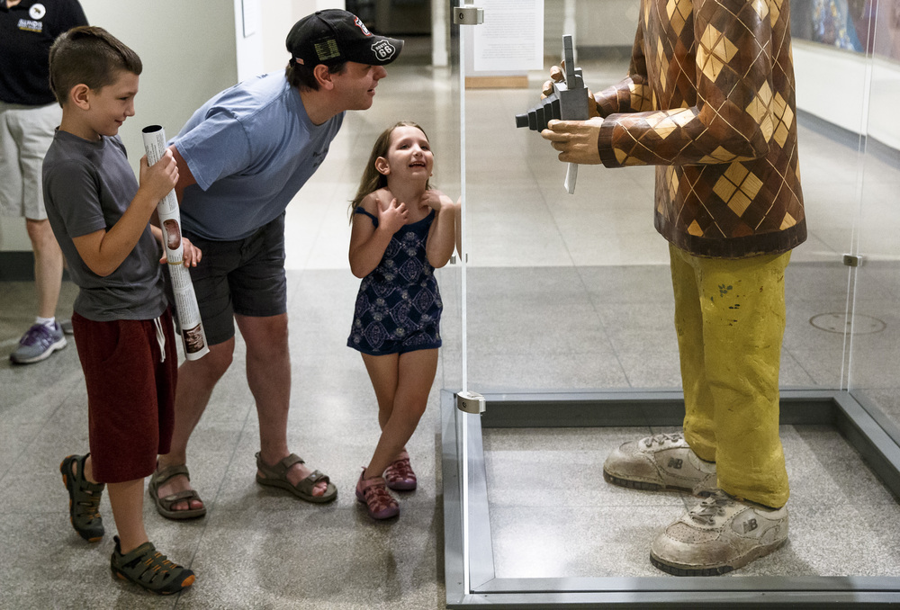 "Josh Friedrich, center, peers through the lens of a sculpture entitled ""Rusty Finnegan"" by Michael Ferris, Jr., while visiting the art exhibits on the second floor with his children Charles, 9, left, and Elizabeth, 5, right, during the reopening of the Illinois State Museum, Saturday, July 2, 2016, in Springfield, Ill. Justin L. Fowler/The State Journal-Register"