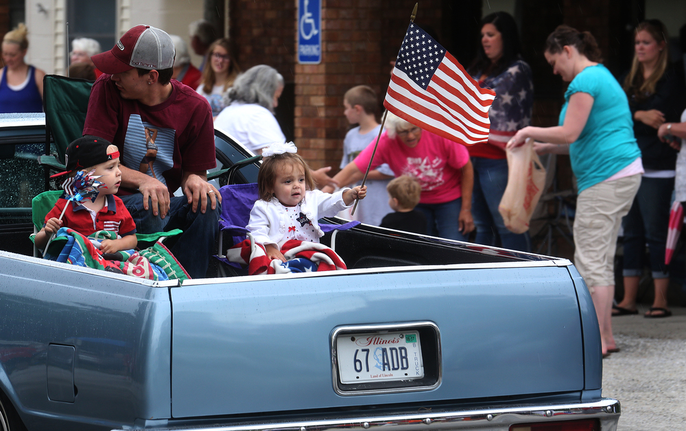 Children seated in miniature lawn chairs riding in the parade got into the spirit, with one waving Old Glory along S. Main Street. David Spencer/The State Journal-Register